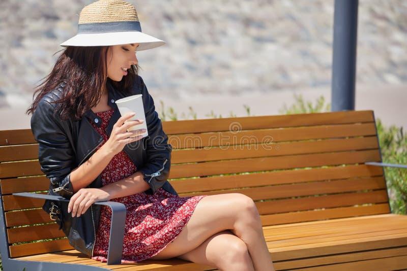 Жизнерадостная женщина в кофе утра улицы выпивая в свете солнечности стоковое изображение