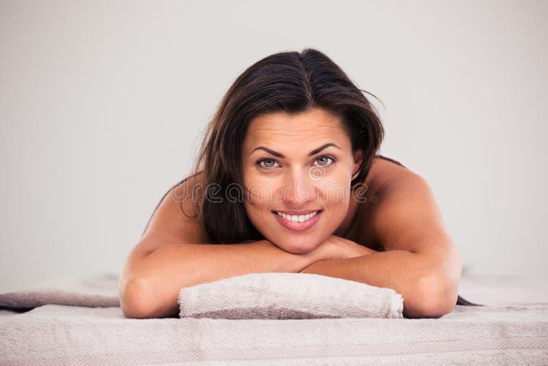 Жизнерадостная женщина лежа на lounger массажа стоковые фото