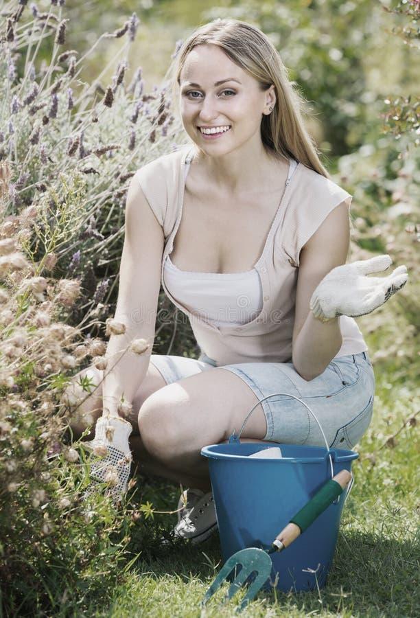 Жизнерадостная женщина засаживая цветки в дворе стоковое фото