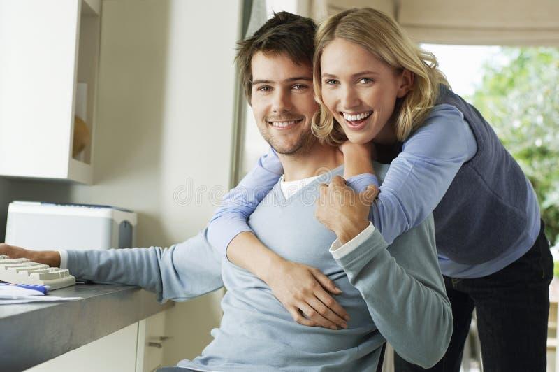 Жизнерадостная женщина обнимая человека от позади стоковая фотография