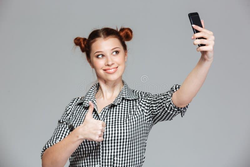 Жизнерадостная женщина показывая большие пальцы руки вверх и принимая selfie с smartphone стоковая фотография