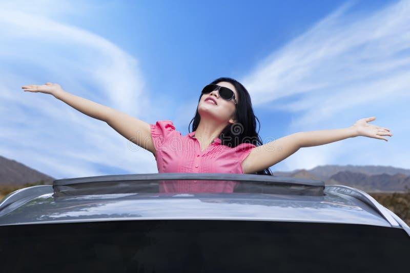 Жизнерадостная женщина стоя на крыше с окошком стоковые изображения rf