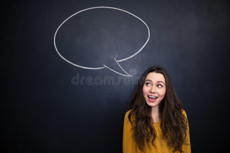 Жизнерадостная женщина усмехаясь над классн классным с пустым пузырем речи стоковая фотография rf