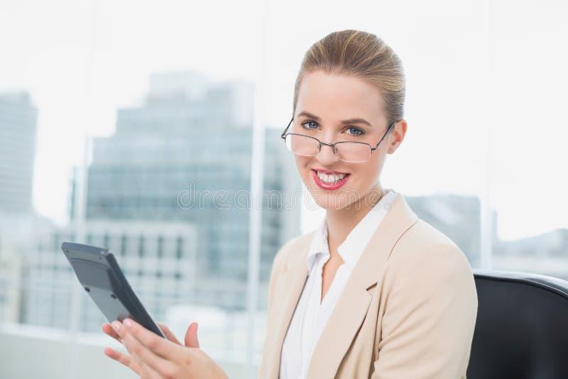 Жизнерадостная коммерсантка с стеклами используя калькулятор стоковые фото