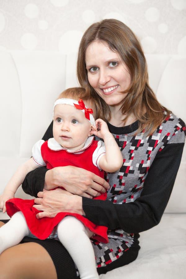 Жизнерадостная мать с ее малой дочерью на коленях стоковые изображения rf