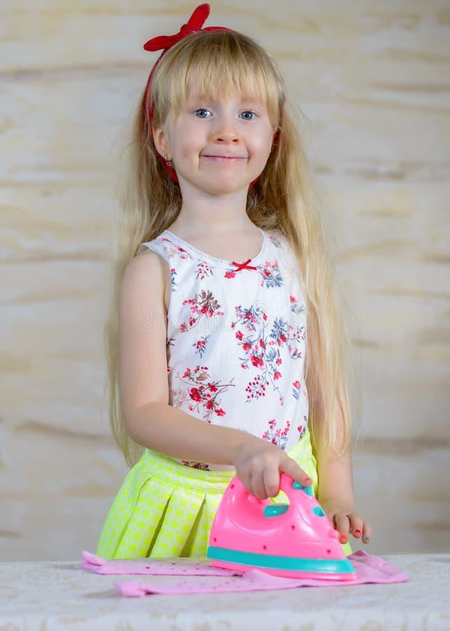 Жизнерадостная маленькая девочка используя утюг игрушки стоковые изображения