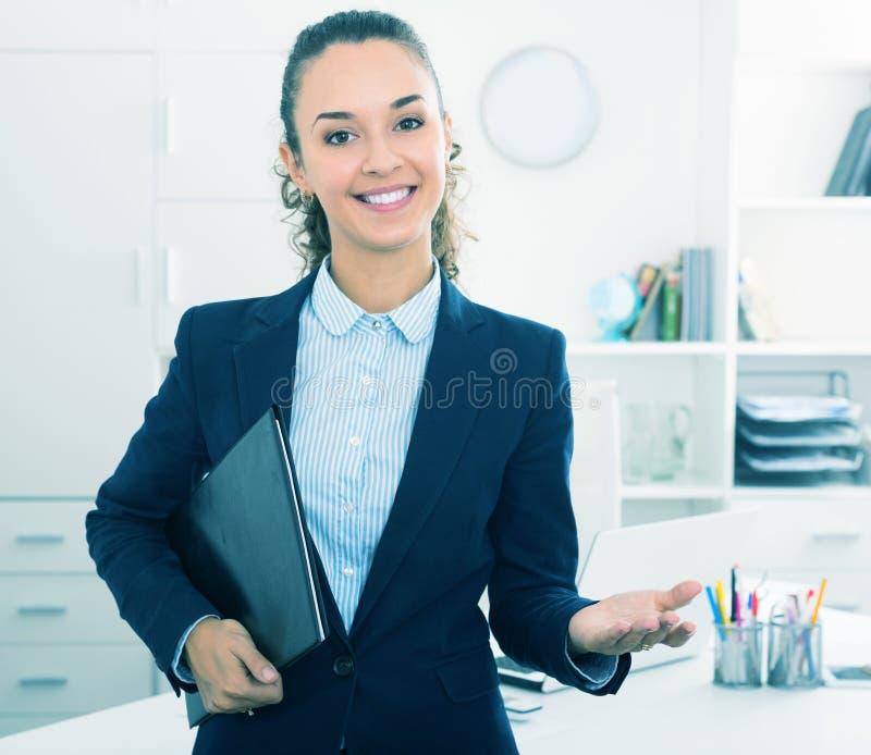 Жизнерадостная молодая женщина держа документы в руках стоковое фото