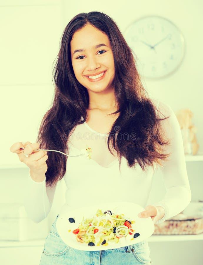 Жизнерадостная молодая женщина имеет обед дома стоковое изображение rf