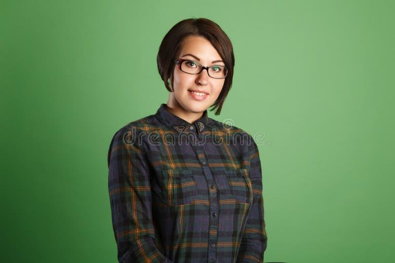 Жизнерадостная молодая женщина на зеленой предпосылке стоковая фотография