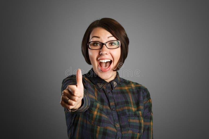 Жизнерадостная молодая женщина показывая большой палец руки вверх по знаку на серой предпосылке стоковое фото
