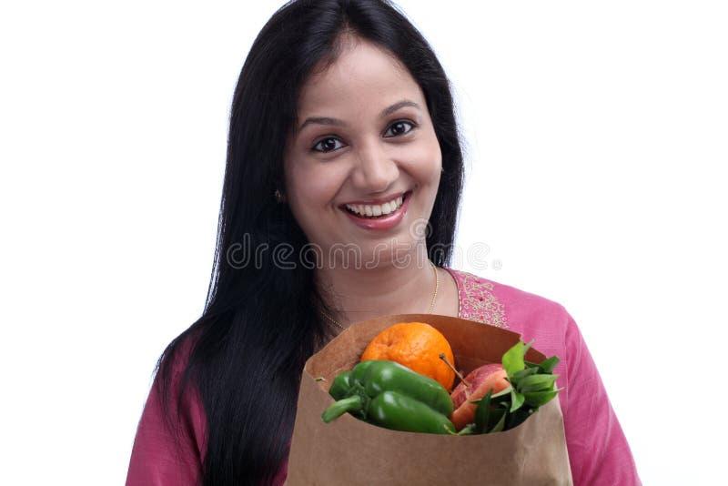 Жизнерадостная молодая женщина с продуктовой сумкой полной плодоовощей и veget стоковое изображение