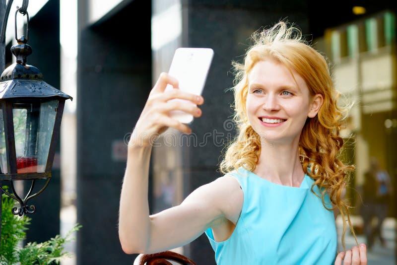 Жизнерадостная молодая женщина фотографируя на телефоне стоковое фото rf