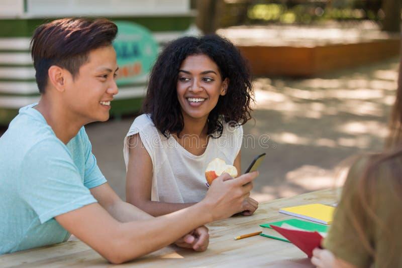 Жизнерадостная молодая многонациональная группа в составе студенты друзей говоря используя телефон стоковое фото