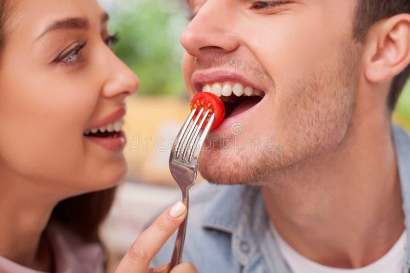 Жизнерадостная молодая любящая пара ест внутри стоковые изображения rf