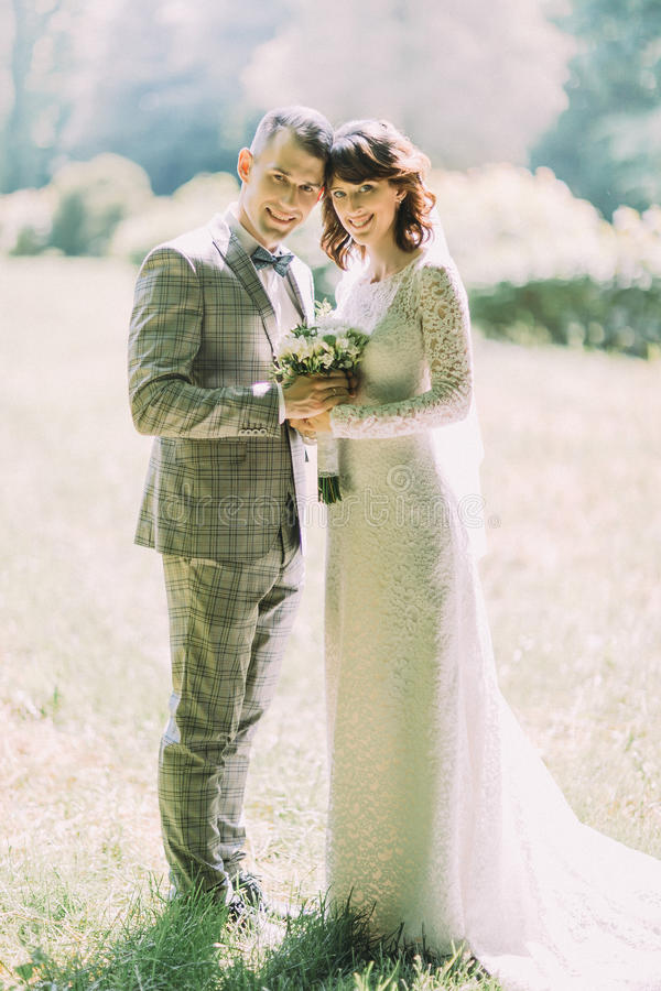 Жизнерадостная пара новобрачных держит букет свадьбы пока тратящ парк времени весной стоковое изображение