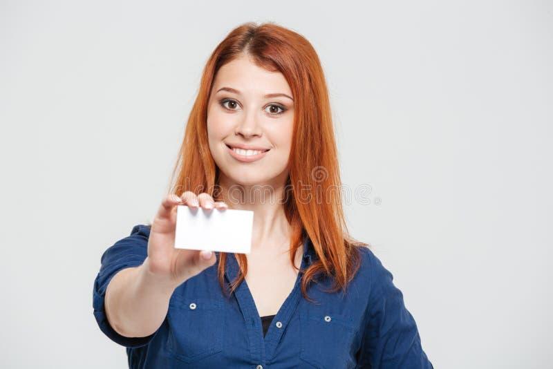 Жизнерадостная привлекательная молодая женщина redhead показывая пустую карточку стоковые изображения