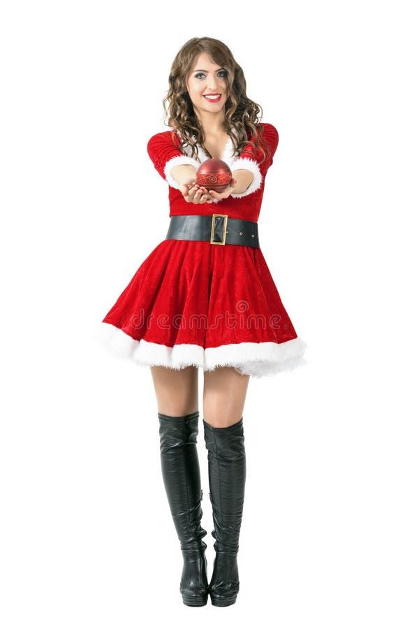 Жизнерадостная дружелюбная девушка Санта Клауса давая вокруг сферы сформировала свечу на камере стоковые изображения