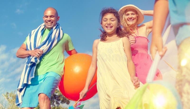 Жизнерадостная семья идя к празднику пляжа наслаждаясь концепцией стоковое фото rf