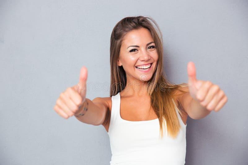 Жизнерадостная симпатичная девушка показывая большие пальцы руки вверх стоковое изображение rf