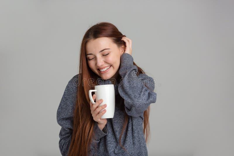 Жизнерадостная симпатичная женщина с кофе и усмехаться длинных волос выпивая стоковые фотографии rf