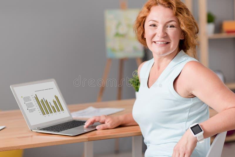 Жизнерадостная старшая женщина сидя на таблице стоковое изображение rf