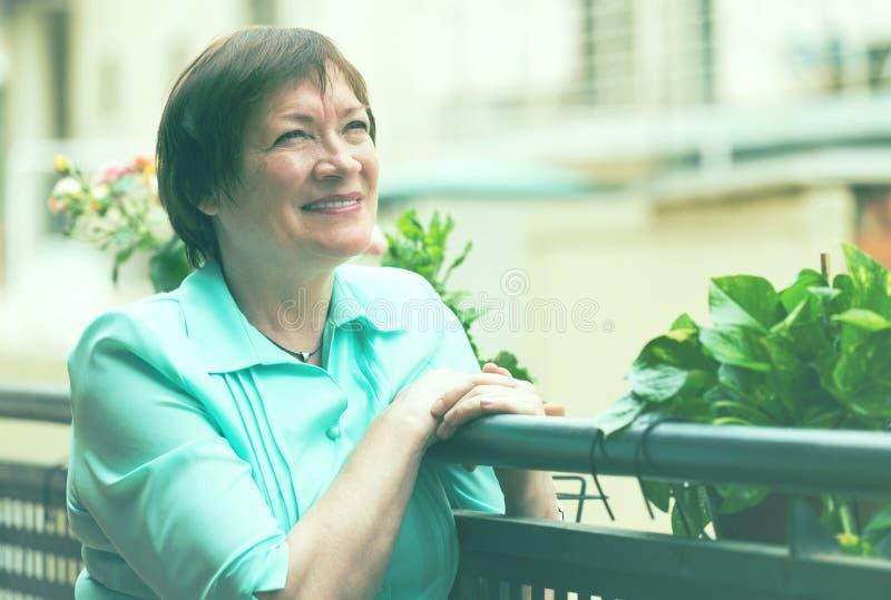 Жизнерадостная старшая женщина сидя на террасе стоковое изображение rf