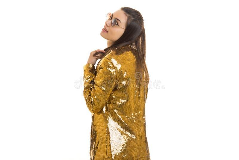 Жизнерадостная стильная маленькая девочка в золотой куртке и круглых солнечных очках стоковая фотография rf