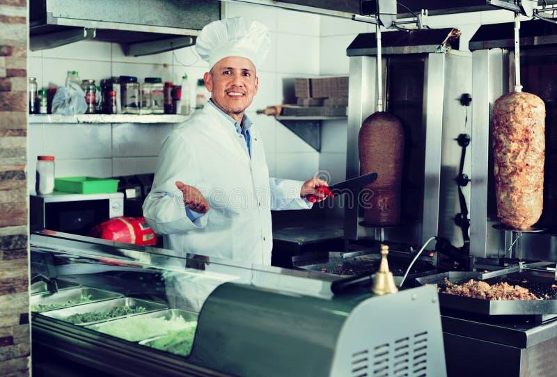 Жизнерадостное зрелое мясо kebab вырезывания кашевара человека на кухне стоковое фото