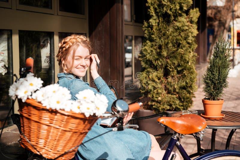 Жизнерадостное сочинительство женщины в тетради и усмехаться на стенде outdoors стоковое изображение