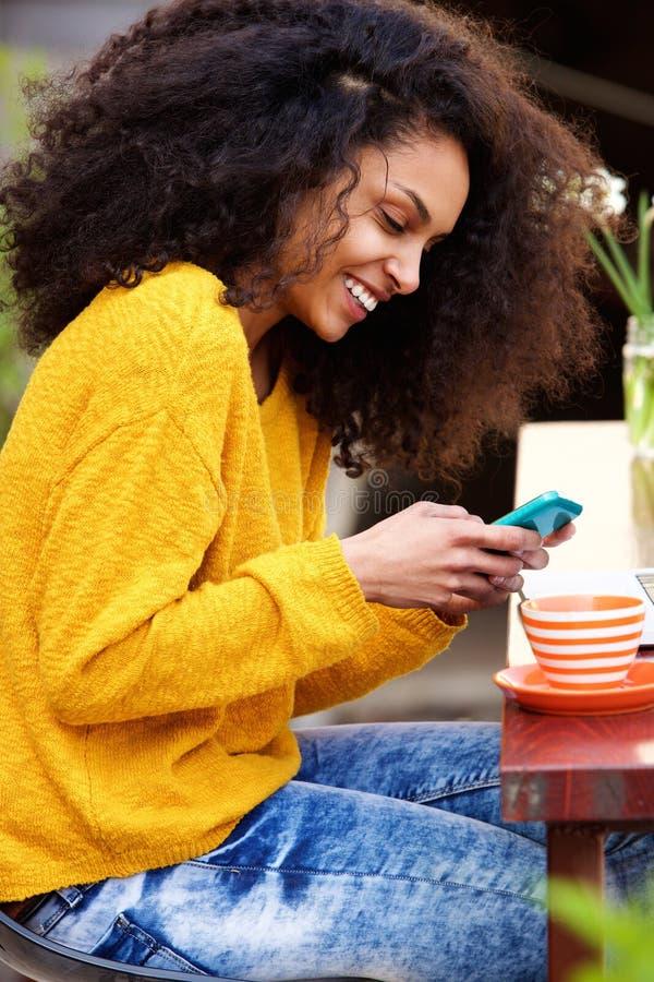 Жизнерадостное текстовое сообщение чтения женщины на мобильном телефоне на кафе стоковое фото rf