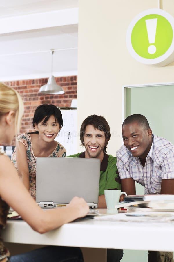 Жизнерадостные бизнесмены используя компьтер-книжку в офисе стоковое фото rf