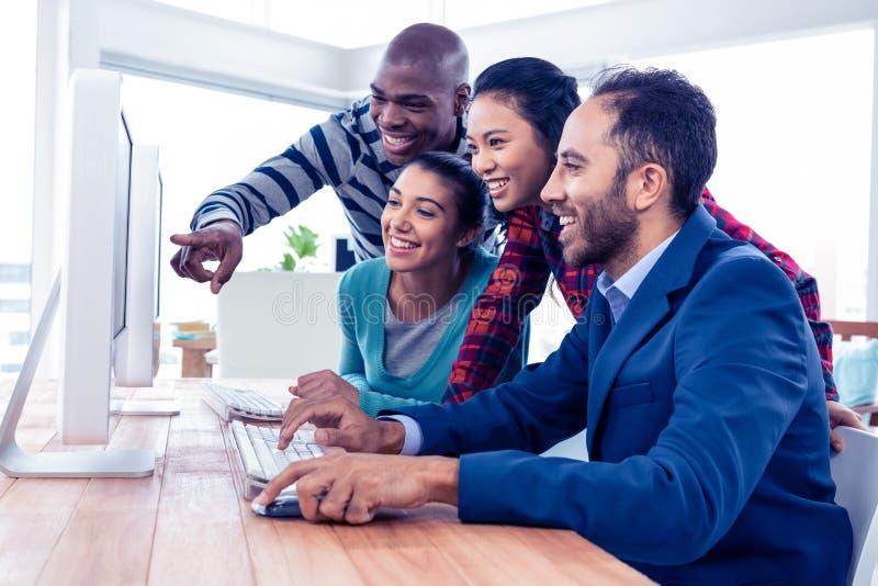 Жизнерадостные бизнесмены смотря экран компьютера стоковые изображения