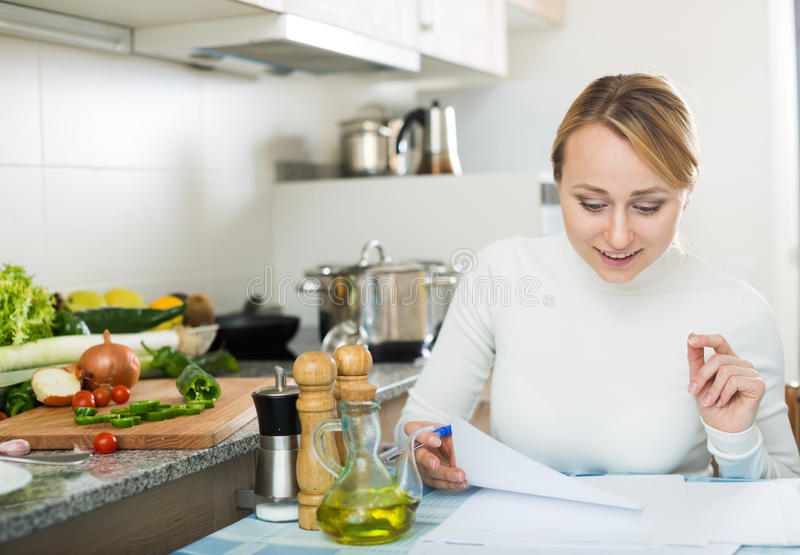 Жизнерадостные бумаги подписания домохозяйки в кухне стоковое изображение