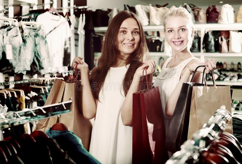 Жизнерадостные девушки имея много хозяйственных сумок стоковые фото