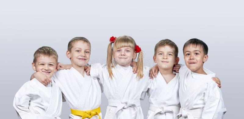 Жизнерадостные дети в karategi на серой предпосылке стоковые фото