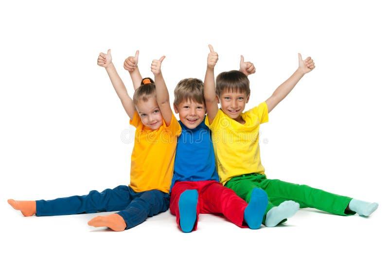 Жизнерадостные дети держат их большие пальцы руки вверх стоковые фото