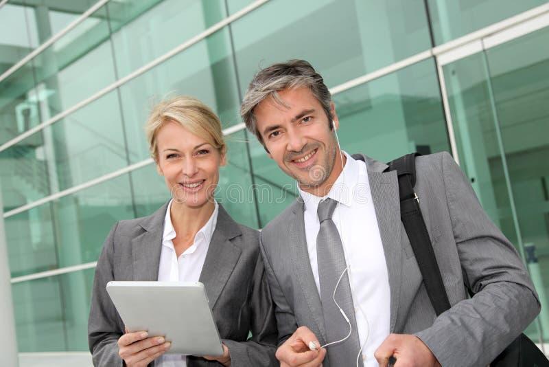 Жизнерадостные деловые партнеры используя таблетку стоковые фотографии rf