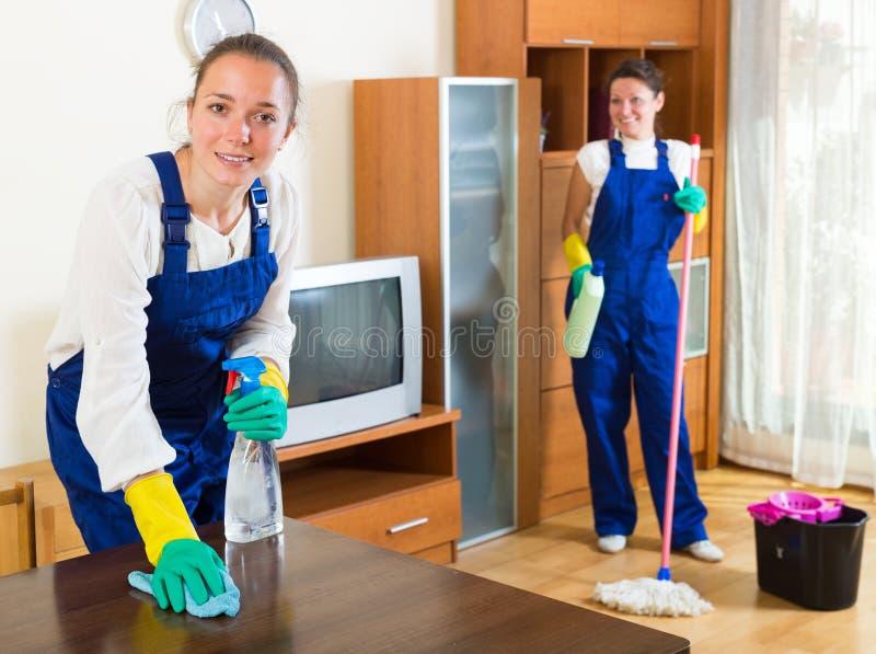 Жизнерадостные женщины в форме делая домашнее хозяйство стоковое фото