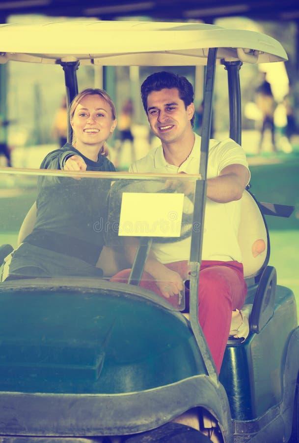 Жизнерадостные игроки в гольф человека и женщины ехать тележка гольфа стоковые изображения rf