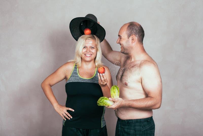 Жизнерадостные корпулентные пары с фруктом и овощем стоковые изображения rf