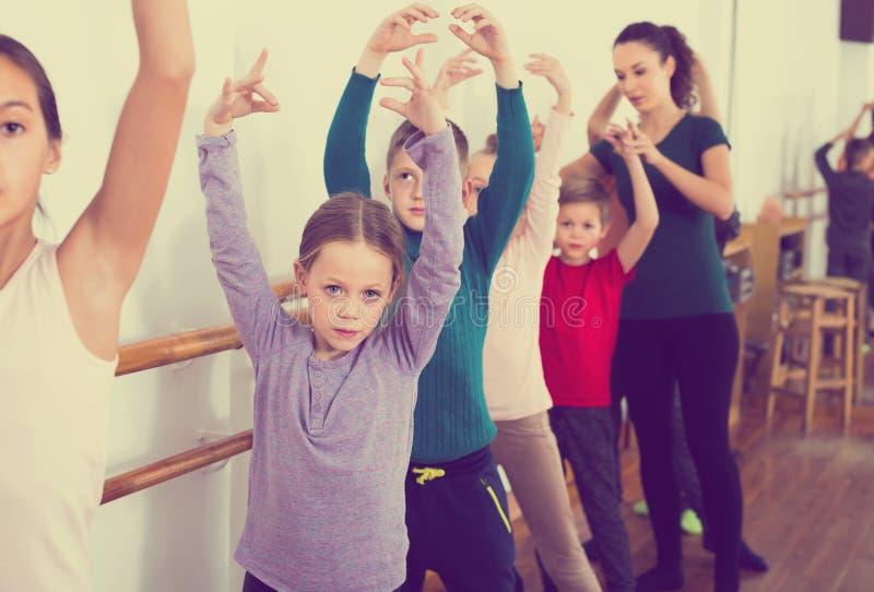 Жизнерадостные мальчики и девушки репетируя балет танцуют в студии стоковое фото