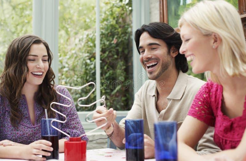Жизнерадостные многонациональные друзья на таблице Verandah стоковое изображение