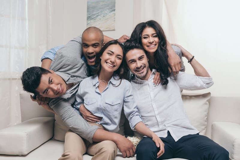 Жизнерадостные многонациональные друзья обнимая пока сидящ на софе дома стоковое изображение rf