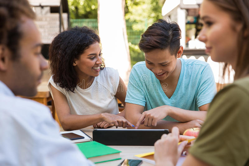 Жизнерадостные молодые многонациональные студенты друзей outdoors используя таблетку стоковое изображение rf