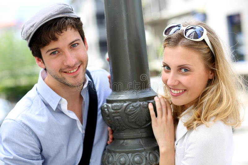 Жизнерадостные молодые пары stynding уличным фонарем стоковое фото