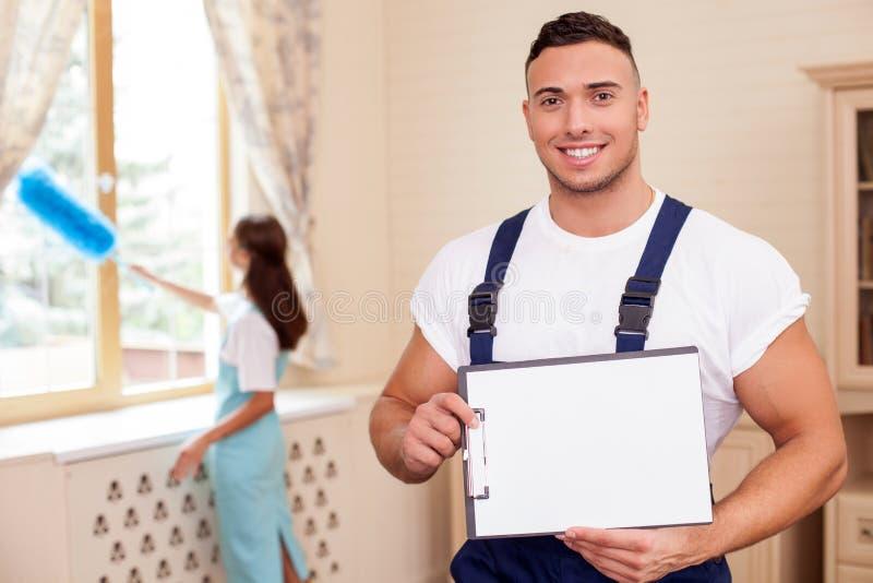 Жизнерадостные молодые уборщики делают домашнее хозяйство с стоковые фотографии rf