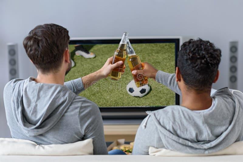 Жизнерадостные мужские друзья развлекая с ТВ стоковое изображение
