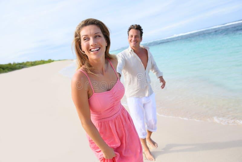 Жизнерадостные пары бежать на пляже стоковая фотография