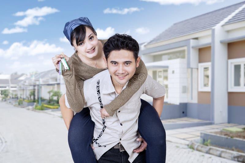 Жизнерадостные пары показывая ключи нового дома стоковая фотография