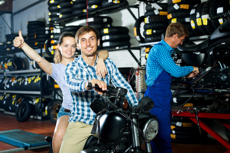 Жизнерадостные пары сидя на мотоцикле на сервисный центр стоковые изображения